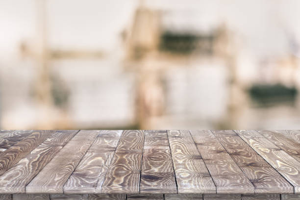 Empty wooden table for product placement Empty wooden table for product placement or montage with focus to table top in the foreground, with white background. Wooden board empty table perspective. workbench stock pictures, royalty-free photos & images