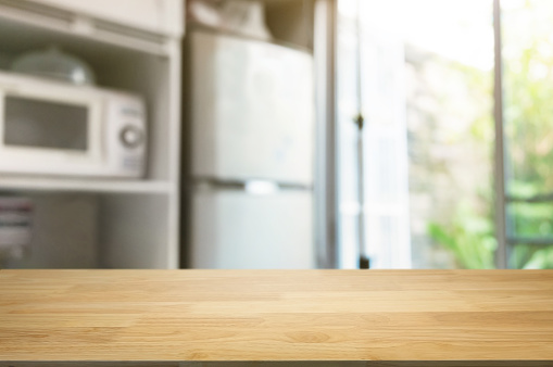 empty wooden table in front of blurred home kitchen background