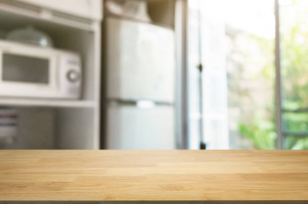 empty wooden table in front of blurred home kitchen background stock photo