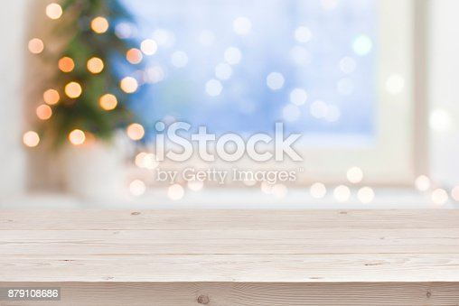 istock Empty wooden table in front of blurred winter holiday background 879108686