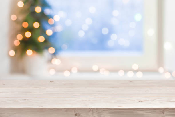 empty wooden table in front of blurred winter holiday background - christmas stock photos and pictures