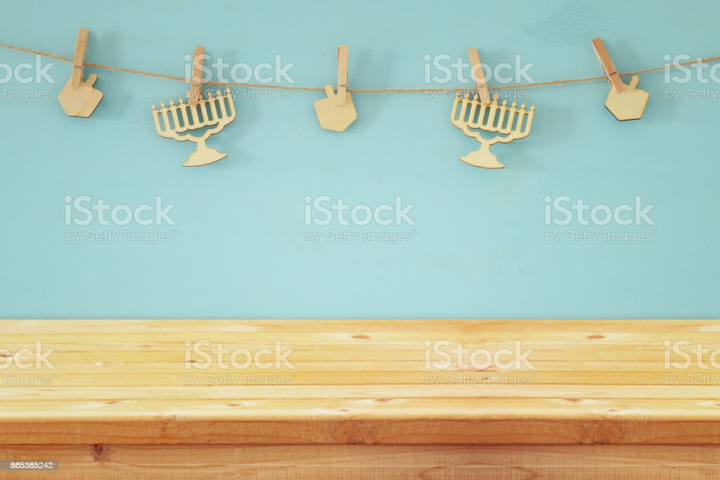 Empty wooden table in front of jewish holiday Hanukkah background with decorative wooden menorah and spinning tops hanging on a rope stock photo