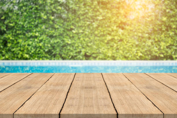 Empty wooden table in front with blurred background of swimming pool Empty wooden table in front with blurred background of swimming pool poolside stock pictures, royalty-free photos & images