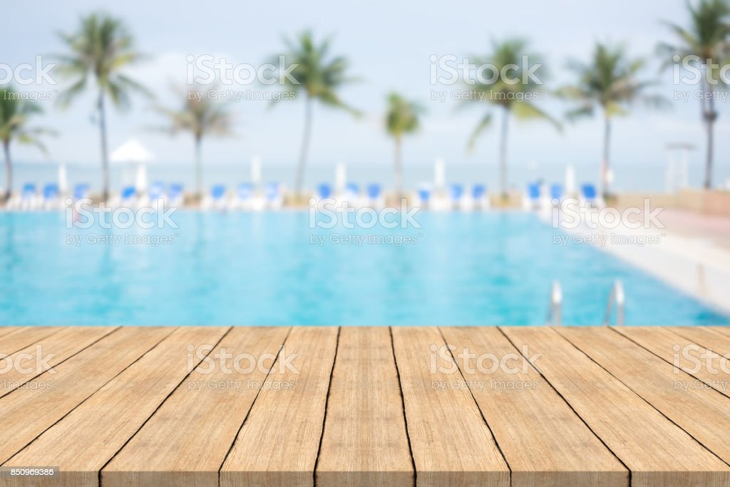 Empty wooden table in front with blurred background of swimming pool at beach,space for montage products stock photo