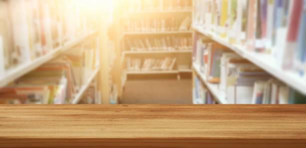 leere holztisch in bibliothek. bildung und lernkonzept. - geführtes lesen stock-fotos und bilder