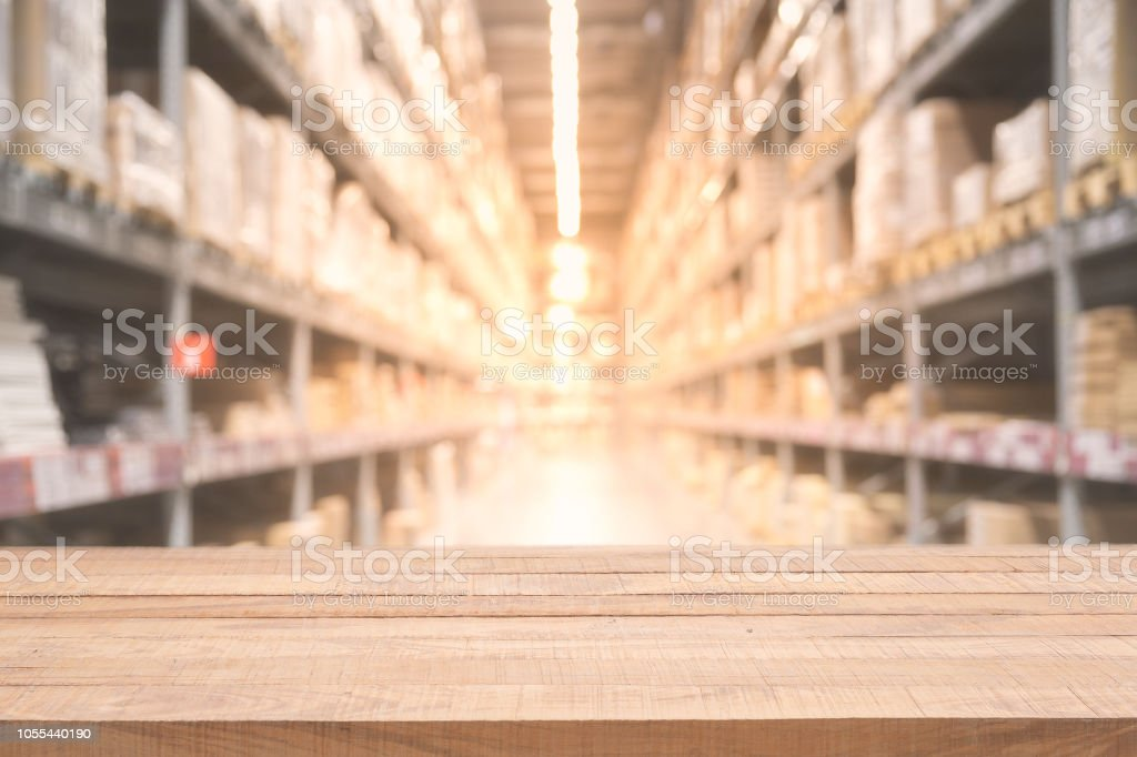 Empty wooden table on defocused blurred boxes on rows of shelves in...