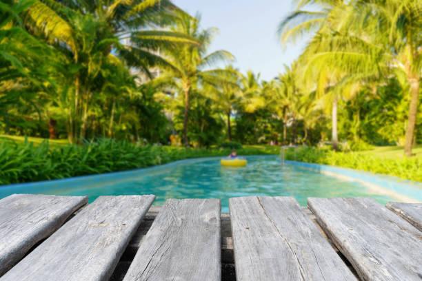 mesa de madera vacía en el fondo borroso de la piscina - foto de stock