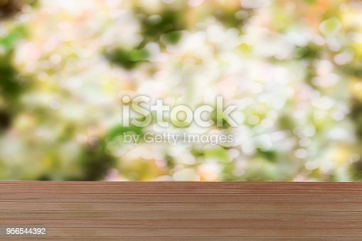 948743278istockphoto Empty wooden table over blurred blooming cherries background. Spring background 956544392