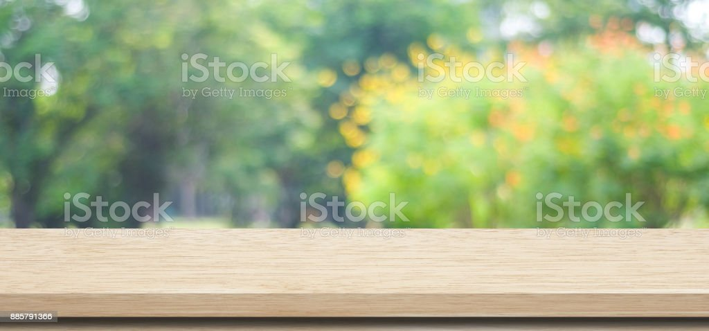 Empty wooden table over blurred tree park nature with bokeh...