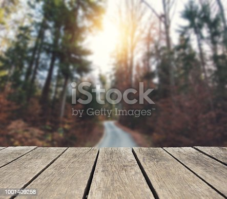 Empty wooden table over defocused autumn background