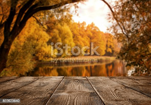 istock Empty wooden table over the autumn landscape 822623640
