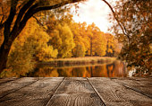 Autumn background, close up of old empty wooden table over the lake with copy space