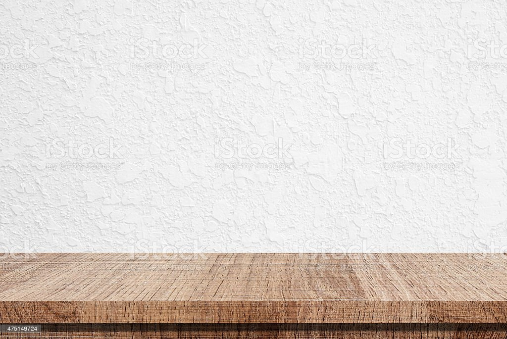 Empty wooden table over white cement wall background stock photo