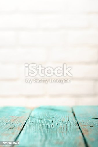 471504772 istock photo Empty wooden table painted turquoise and white brick wall copyspace 539849340