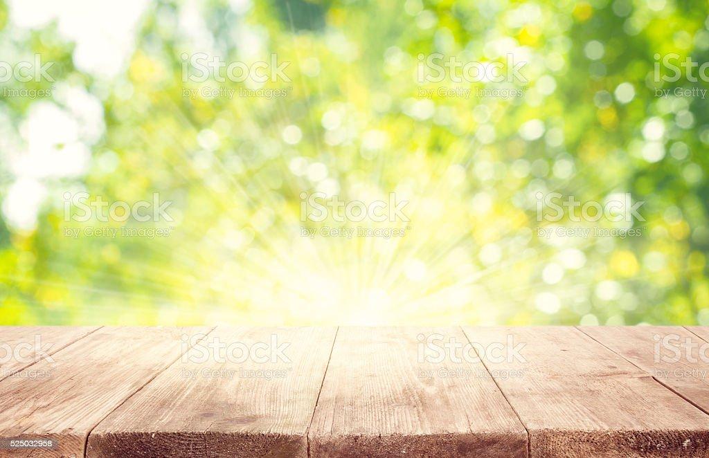 Mesa de madera vacía tablas, verde borrosa fondo de árboles - foto de stock