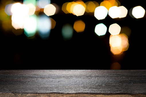 498688230 istock photo Empty wooden table platform and bokeh at night 1064871460