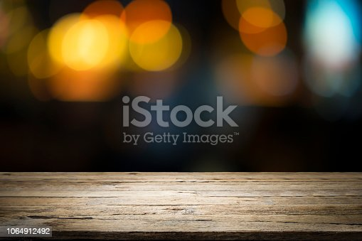 istock Empty wooden table platform and bokeh at night 1064912492