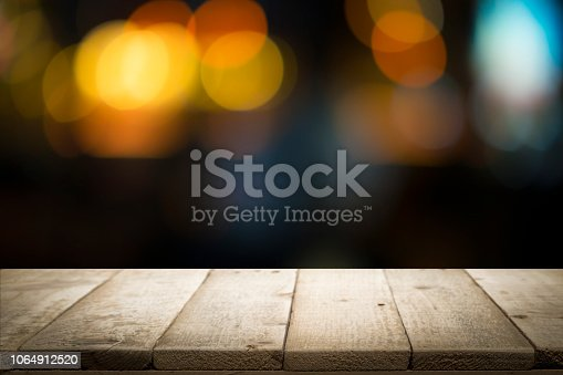 istock Empty wooden table platform and bokeh at night 1064912520