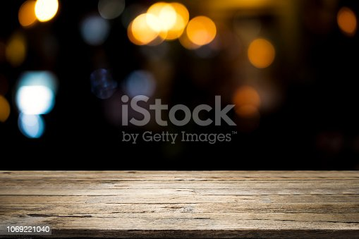 istock Empty wooden table platform and bokeh at night 1069221040