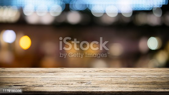 841276202istockphoto Empty wooden table platform and bokeh at night 1179185356
