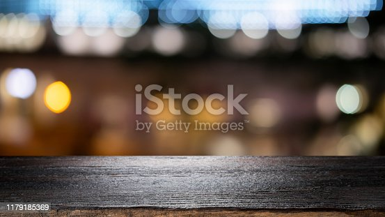 841276206istockphoto Empty wooden table platform and bokeh at night 1179185369