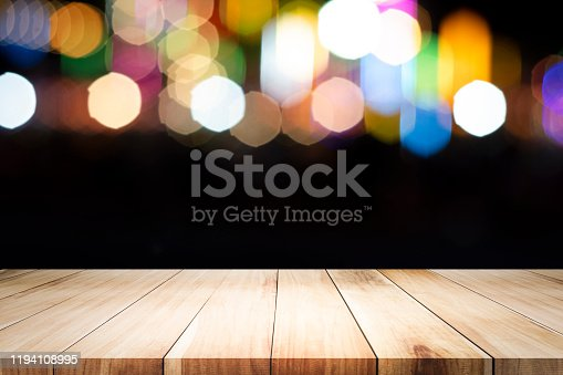 841276206istockphoto Empty wooden table platform and bokeh at night 1194108995