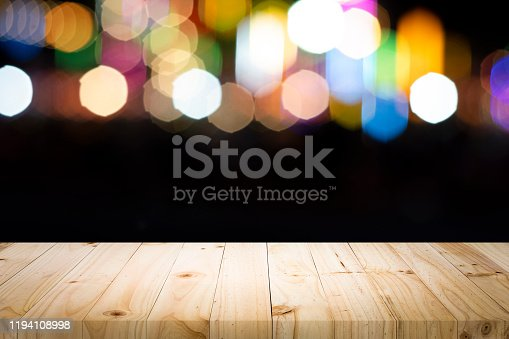 841276202istockphoto Empty wooden table platform and bokeh at night 1194108998