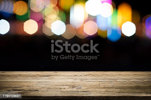 841276202istockphoto Empty wooden table platform and bokeh at night 1194109001