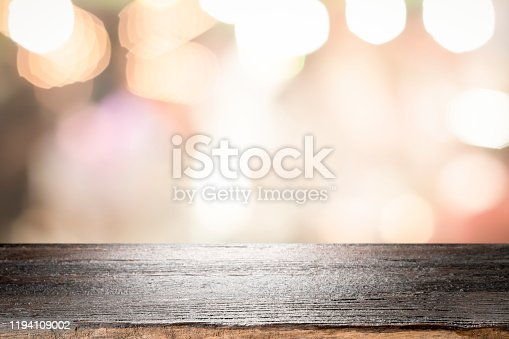 841276206istockphoto Empty wooden table platform and bokeh at night 1194109002