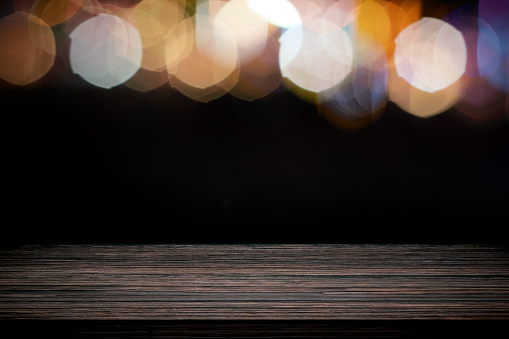 841276206 istock photo Empty wooden table platform and bokeh at night. 1208570669