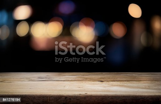 841276202istockphoto Empty wooden table platform and bokeh at night 841276194
