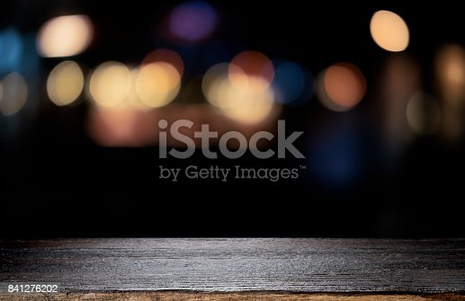 841276202istockphoto Empty wooden table platform and bokeh at night 841276202