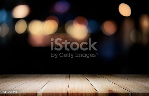 istock Empty wooden table platform and bokeh at night 841276206
