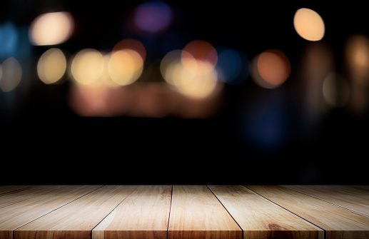 841276206 istock photo Empty wooden table platform and bokeh at night 841276206