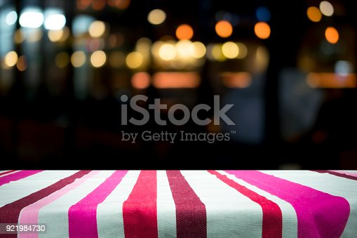 istock Empty wooden table platform and bokeh at night 921984730