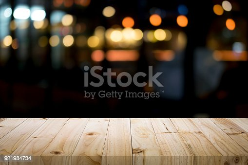 istock Empty wooden table platform and bokeh at night 921984734