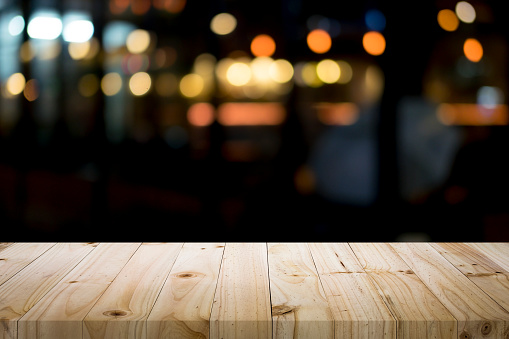 498688230 istock photo Empty wooden table platform and bokeh at night 921984734