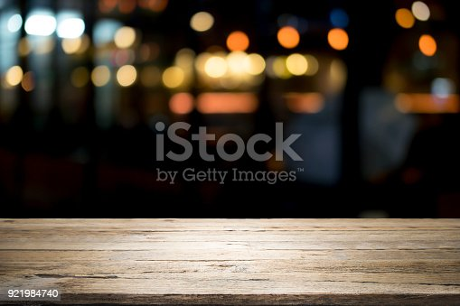 istock Empty wooden table platform and bokeh at night 921984740