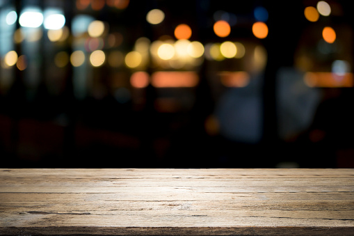 498688230 istock photo Empty wooden table platform and bokeh at night 921984740