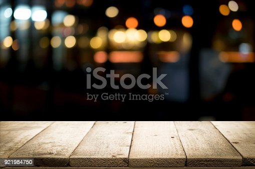 841276206istockphoto Empty wooden table platform and bokeh at night 921984750