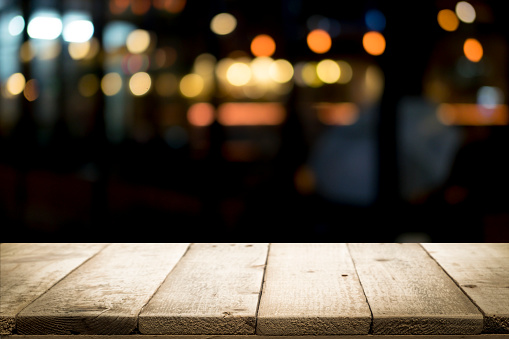 498688230 istock photo Empty wooden table platform and bokeh at night 921984750