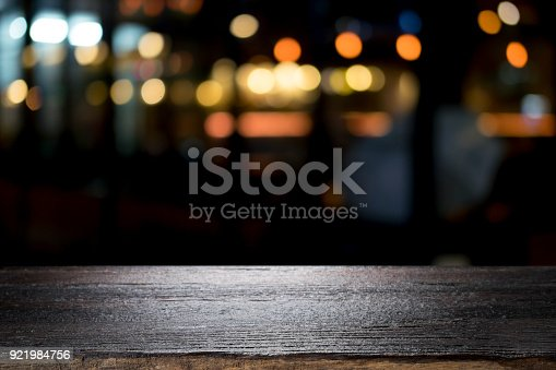 istock Empty wooden table platform and bokeh at night 921984756