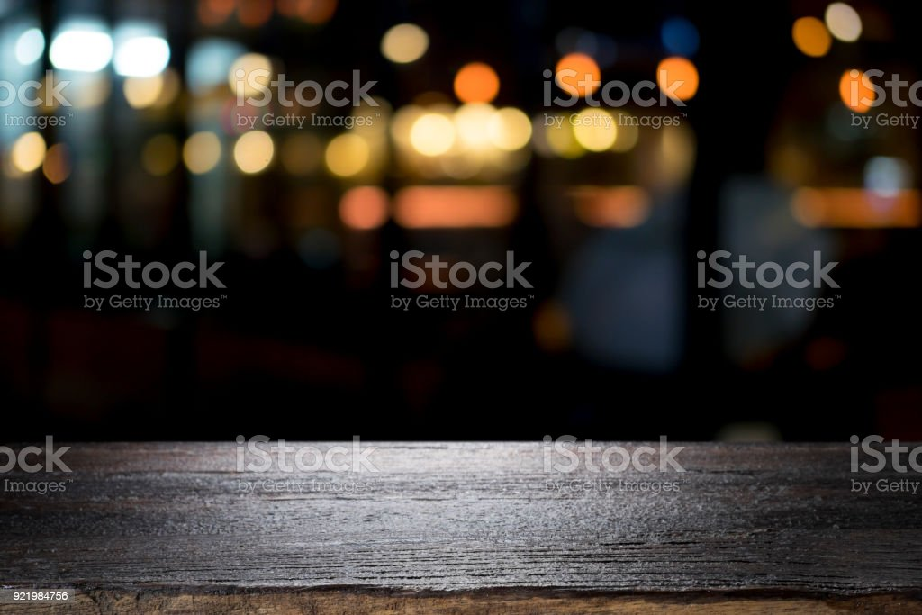 Empty wooden table platform and bokeh at night стоковое фото