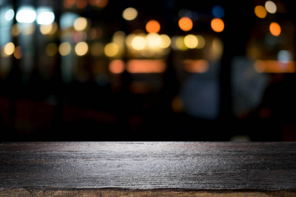 empty wooden table platform and bokeh at night - bar zdjęcia i obrazy z banku zdjęć