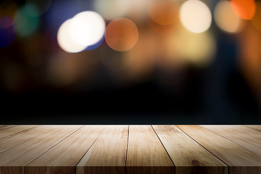 498688230 istock photo Empty wooden table platform and bokeh at night. 949860474