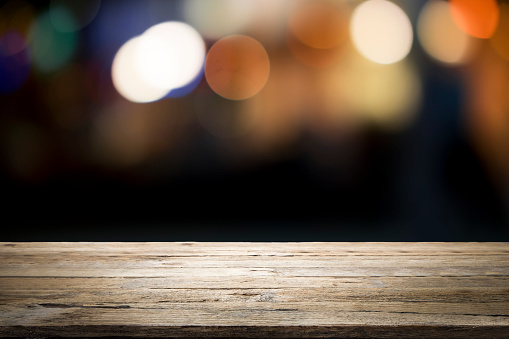 498688230 istock photo Empty wooden table platform and bokeh at night. 949860478