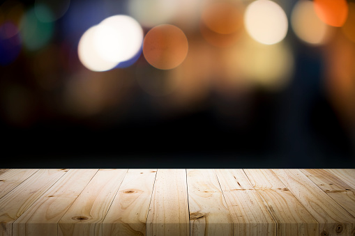 498688230 istock photo Empty wooden table platform and bokeh at night. 949860480