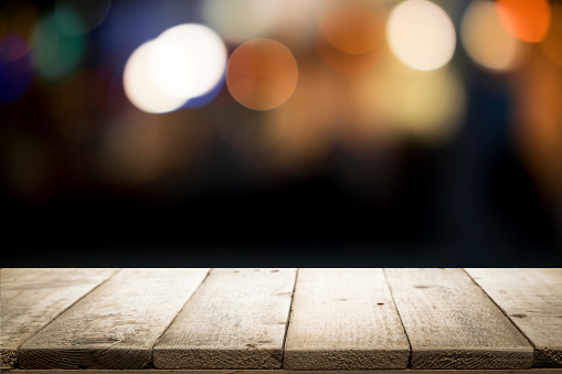 498688230 istock photo Empty wooden table platform and bokeh at night. 949860488