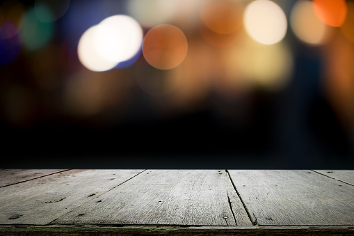 498688230 istock photo Empty wooden table platform and bokeh at night. 949860492