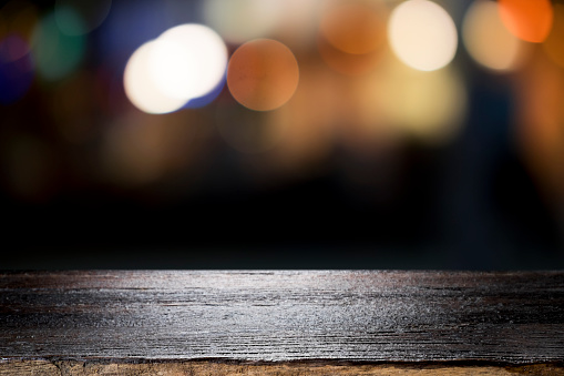 498688230 istock photo Empty wooden table platform and bokeh at night. 949860494